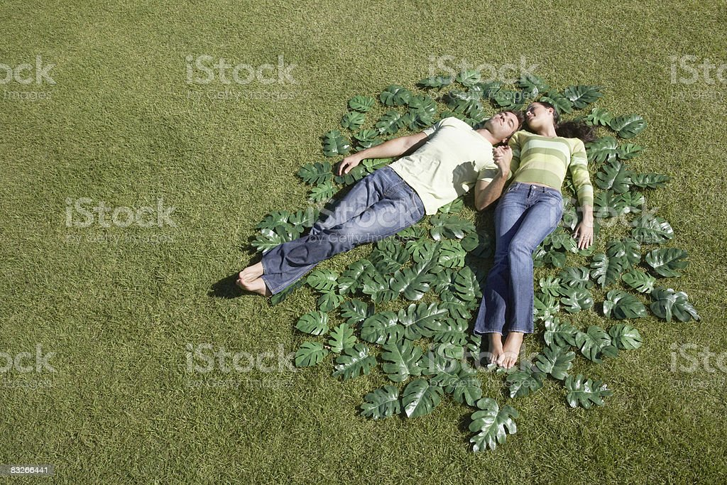 Couple laying on grass surrounded by green leaves royalty free stockfoto