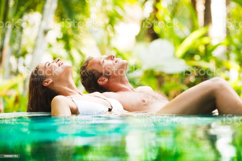 Couple leaned on the edge of a tropical pool. royalty-free stock photo