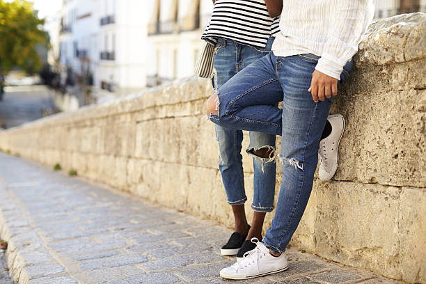 couple leaning against a wall in ibiza, spain, low section - jeans stock photos and pictures