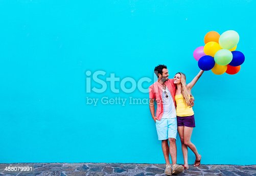 Happy couple with multi coloured balloons against blue wall