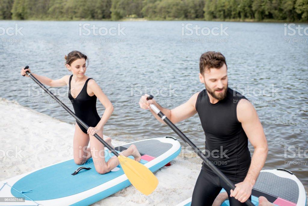 Aprendizagem do casal a linha sobre o paddleboard na praia - Foto de stock de Adulto royalty-free
