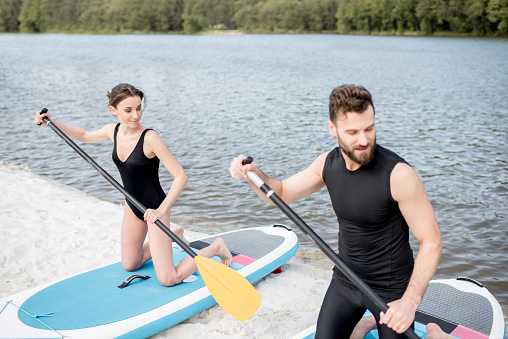 Foto de Aprendizagem Do Casal A Linha Sobre O Paddleboard Na Praia e mais fotos de stock de Adulto