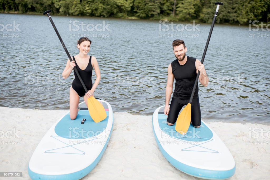 Couple learning to row on the paddleboard on the beach royalty-free stock photo