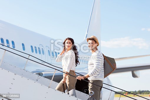 Beautiful young couple boarding a flight. Man and woman going on a holiday.