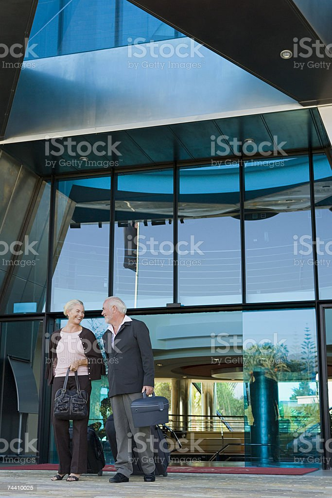 Couple leaving hotel stock photo