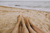Cropped shot of an affectionate couple standing together by the water's edge at the beach