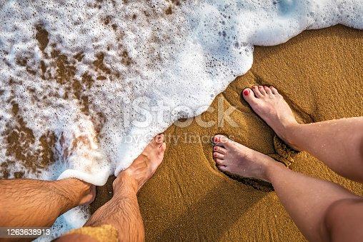 couple legs on the sand at the beach