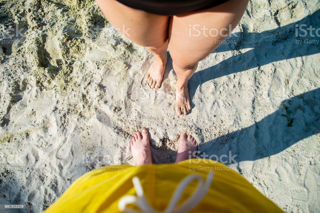 couple legs overhead view on sand beach. summer time
