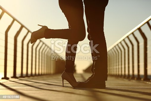 istock Couple legs silhouette hugging with love in a bridge 491923186