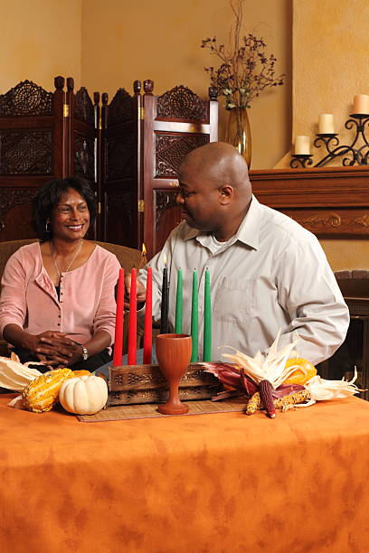 couple lighting kwanzaa candles - kwanzaa stock pictures, royalty-free photos & images