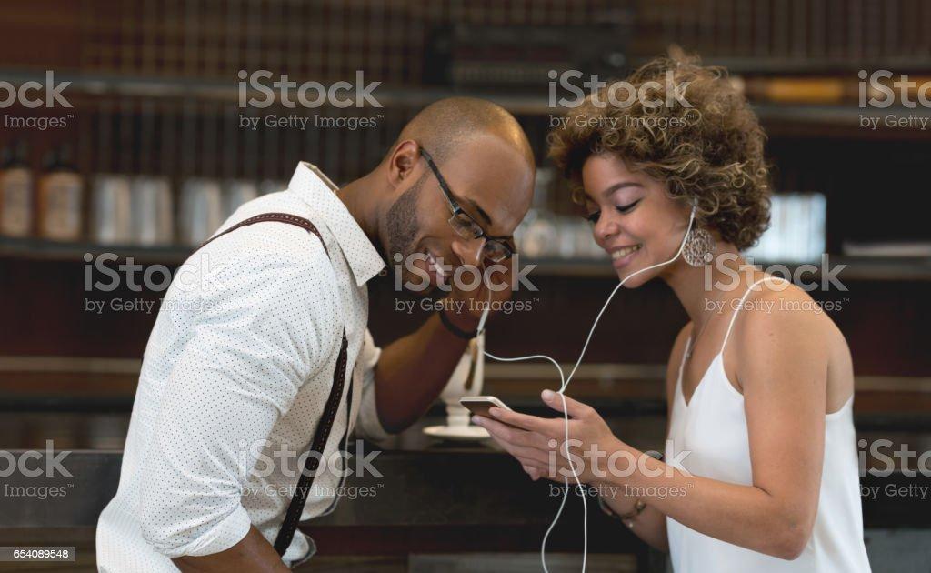 Couple listening to music sharing headphones stock photo