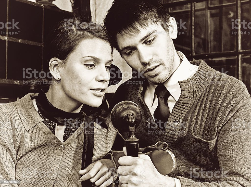 Couple Listening to Phone Call Together stock photo
