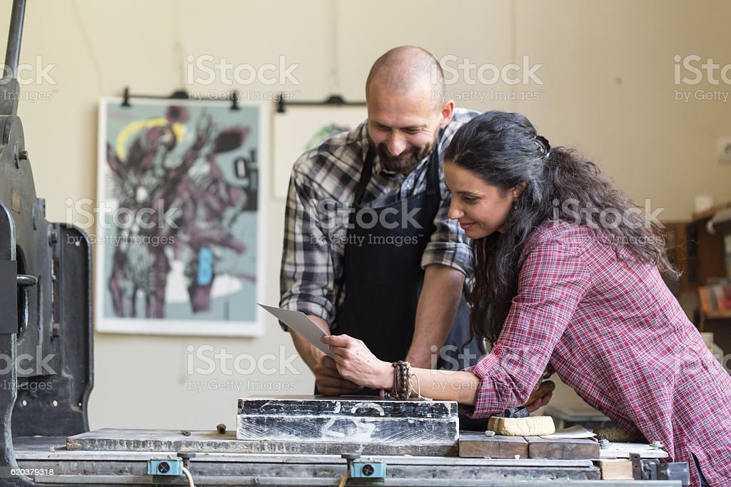 Couple lithography workers looking at new product at workshop zbiór zdjęć royalty-free