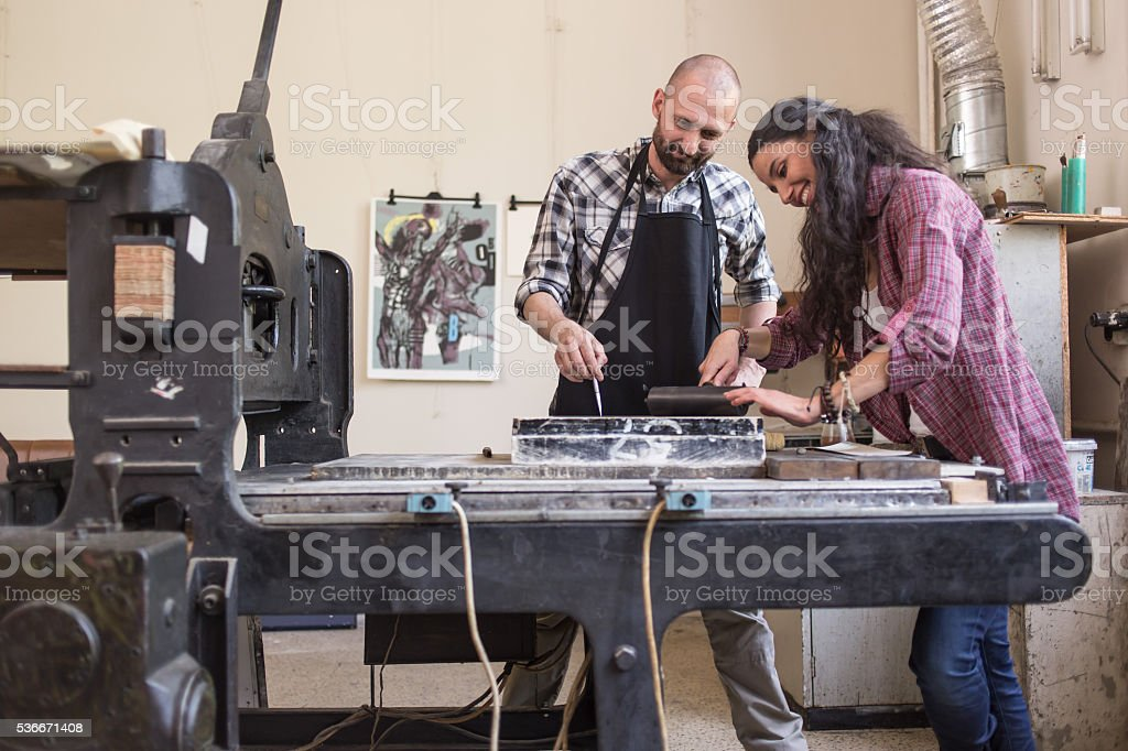 Couple lithography workers using printing press stock photo