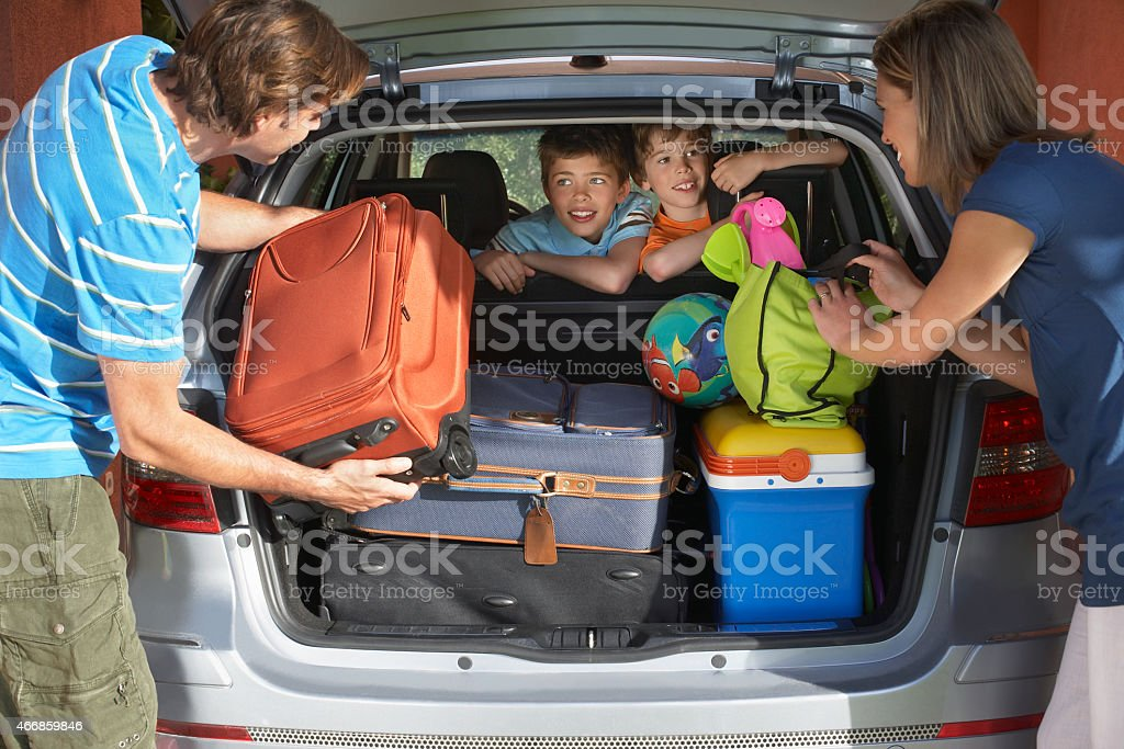 Couple Loading Luggage Into Car Trunk stock photo