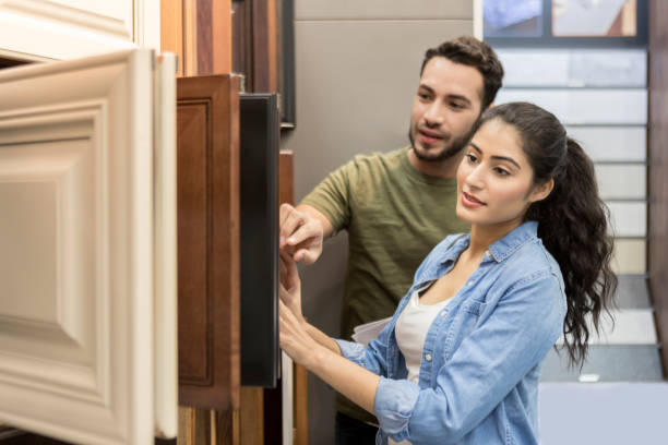 Couple look at cabinet samples in hardware store stock photo