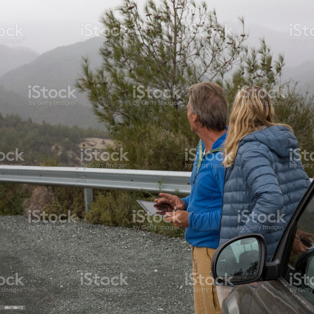 Couple look at digital tablet beside car royalty-free stock photo