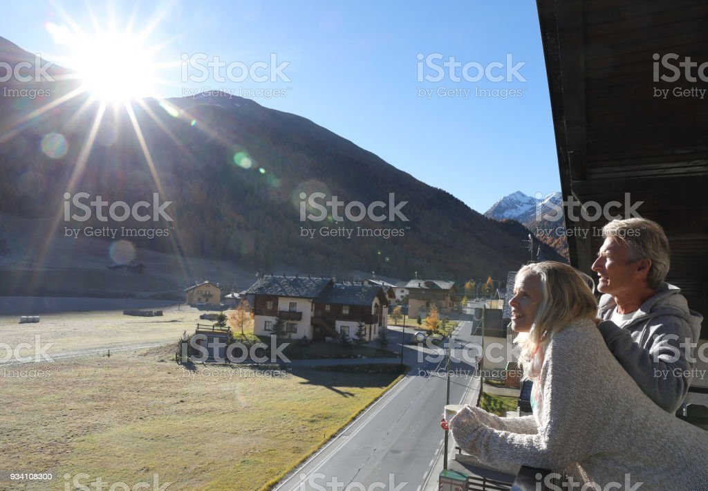 Couple look out over valley from balcony at sunrise. stock photo