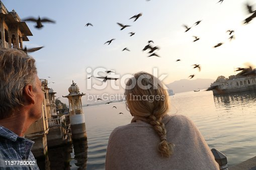 They are at a ghat and pigeons fly overhead