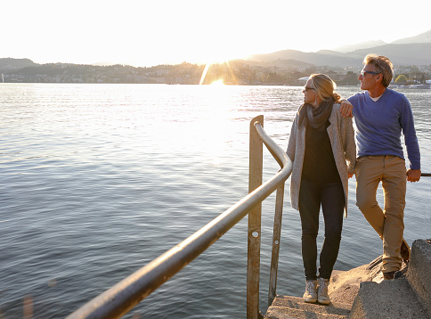 Couple look over lake at sunrise from lakeside walkway