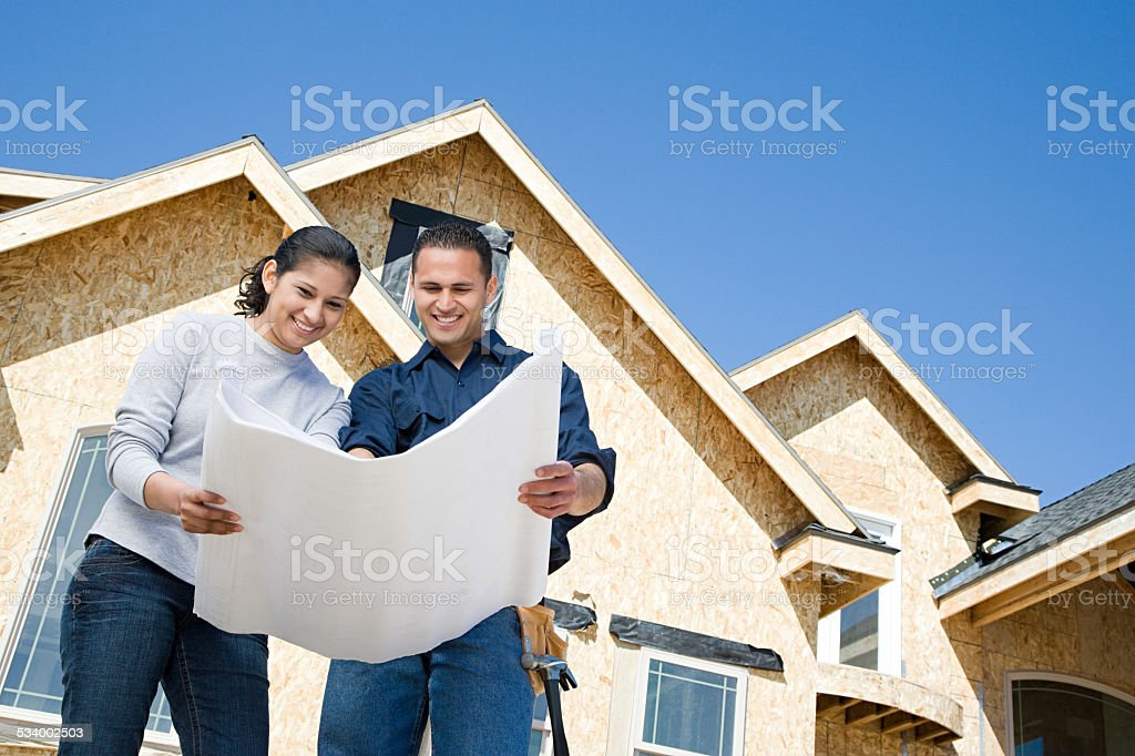 Couple looking at a blueprint stock photo