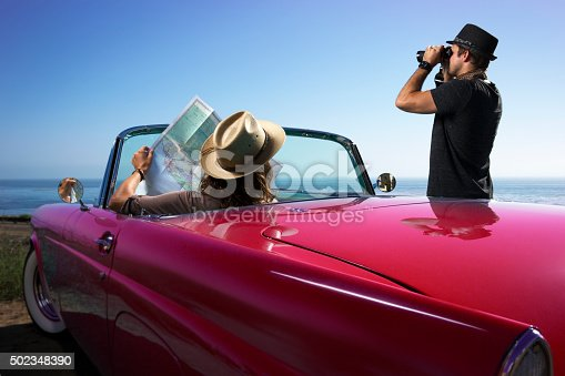 This is a close up photo of a man and woman looking at a map by a blue convertible car.