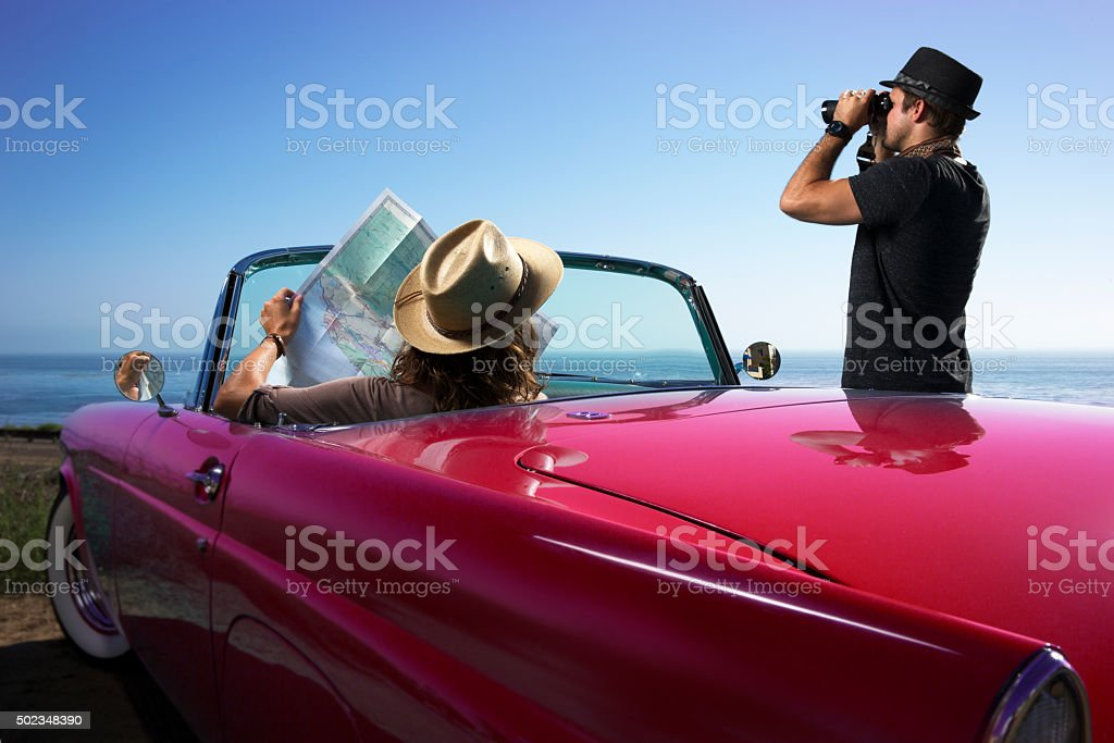 Couple looking at a Road Map in a Blue Convertible Car stock photo