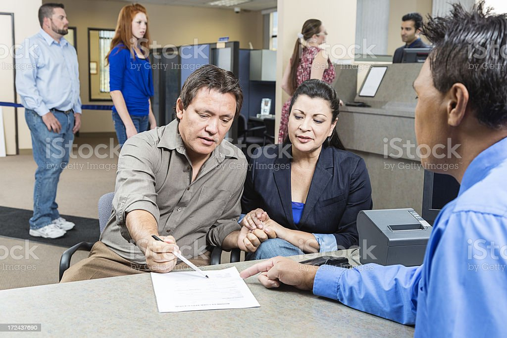 Couple Looking at Application With Banker stock photo