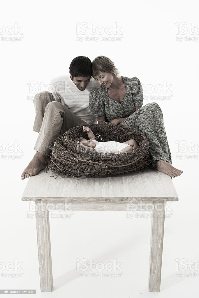 Couple looking at baby girl (2-5 months) lying in bird's nest on wooden table against white background royalty-free stock photo