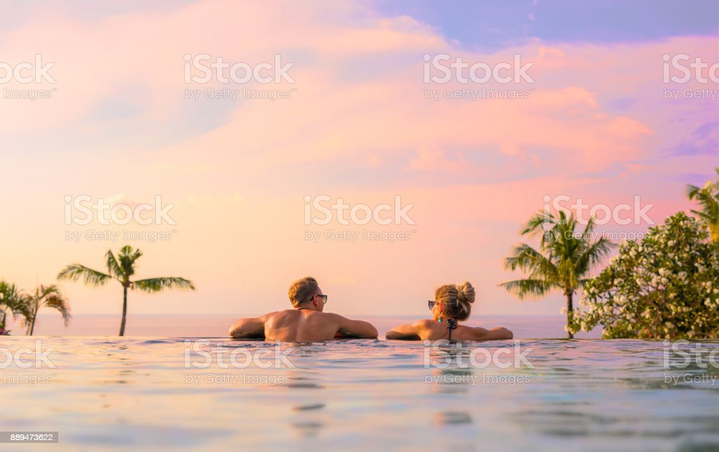 Couple looking at beautiful sunset in infinity pool stock photo