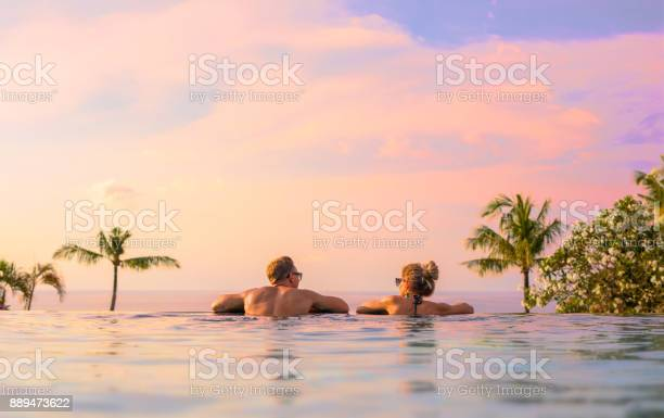 Photo of Couple looking at beautiful sunset in infinity pool