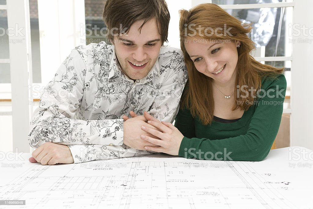 Couple looking at blueprint royalty-free stock photo