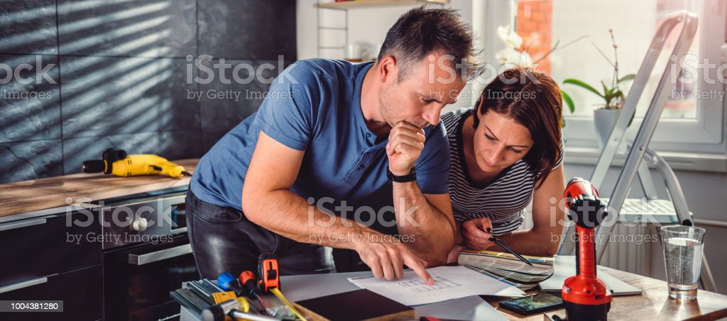 Couple looking at blueprints during kitchen renovation stock photo
