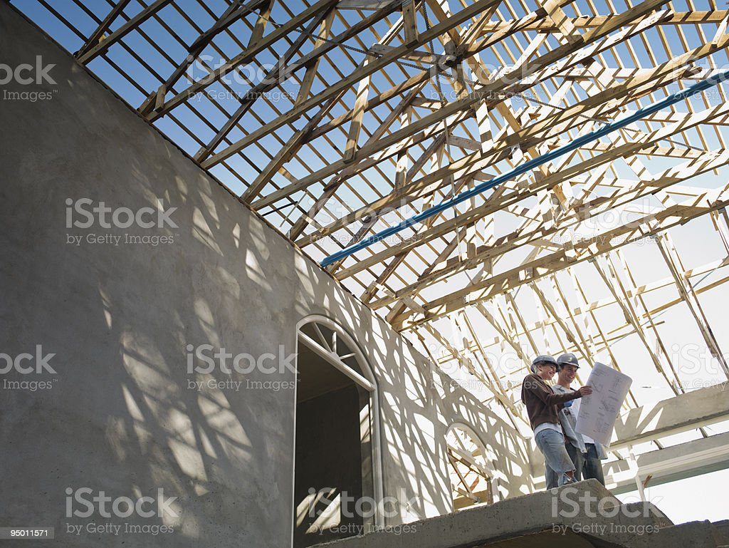Couple looking at blueprints in house under construction stock photo