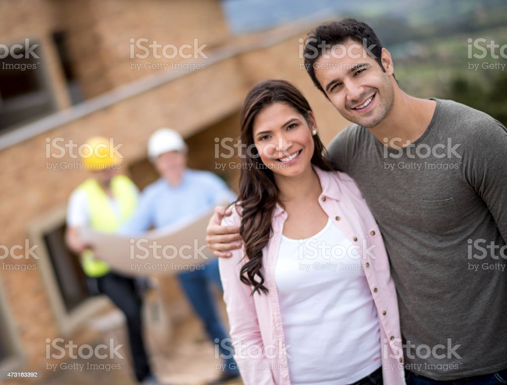 Couple looking at blueprints of a house stock photo