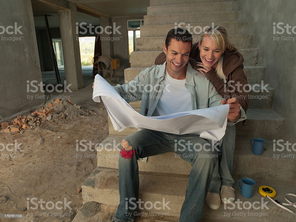 Couple looking at blueprints on staircase of house under construction royalty-free stock photo