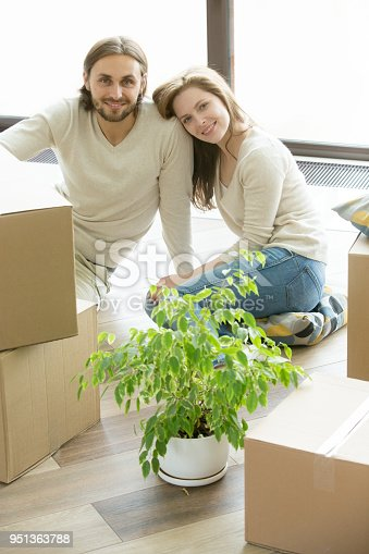 938682826istockphoto Couple looking at camera sitting on floor with boxes, vertical 951363788