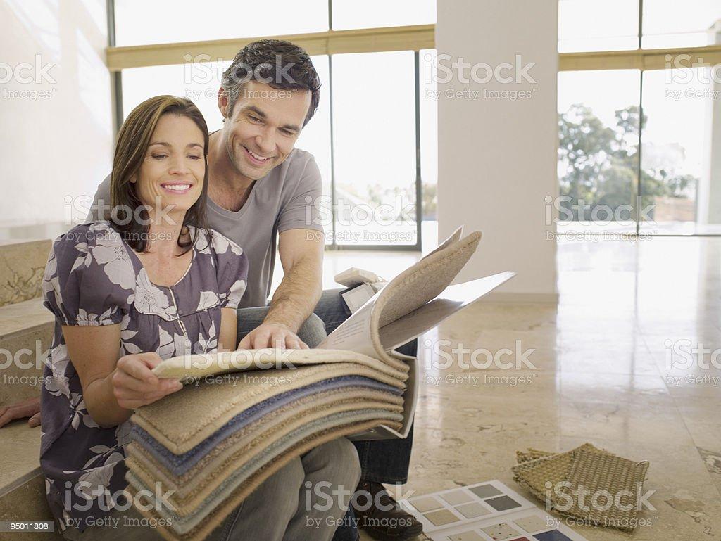 Casal olhando no vazia com tapete amostras em casa - foto de acervo
