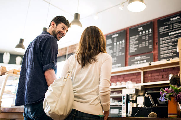 couple looking at coffee shop menu - being in a relationship with someone is going to require stock photos and pictures