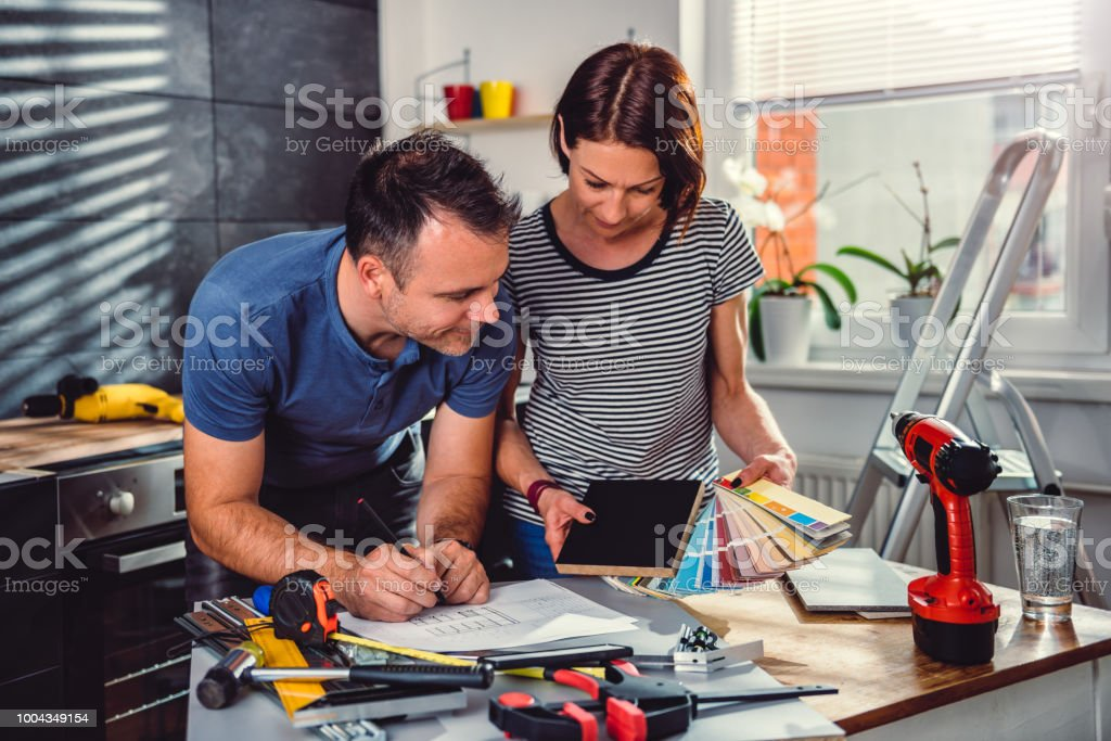 Couple looking at color swatch during kitchen renovation stock photo