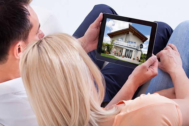 paar blick auf digitale tablet - sofa online kaufen stock-fotos und bilder