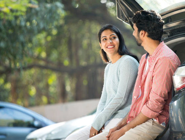 Couple looking at each other in car trunk stock photo
