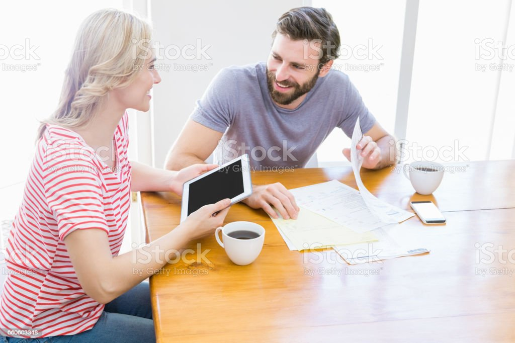 Couple looking at each other while using digital tablet royalty-free stock photo
