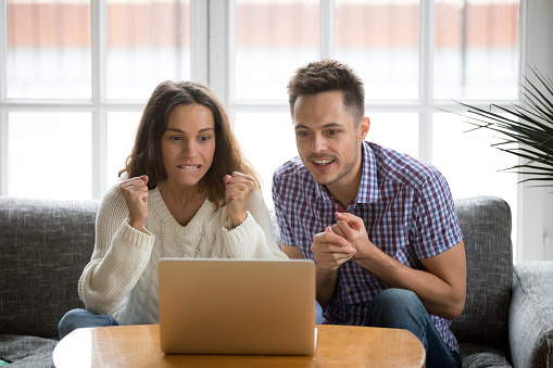 Couple Looking At Laptop Screen Supporting Team Watching Match Online Stock Photo - Download Image Now