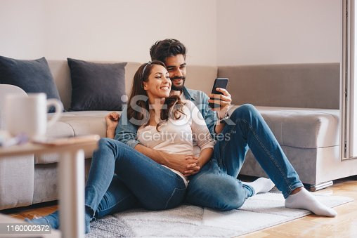 Couple looking at mobile phone at home.