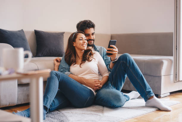 couple looking at mobile phone at home. - guy sofa foto e immagini stock