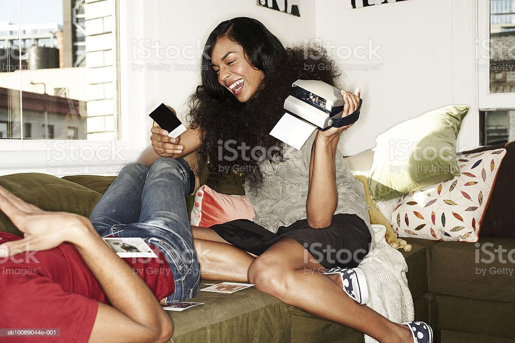 Couple looking at photographs on sofa, laughing royalty free stockfoto