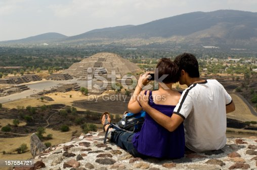 A couple sitting on top of the Pyramid of the Sun, admiring and photographing the ancient Pyramid of the Moon in the archeological area of Teotihuacan, close to Mexico City, Mexico. Unesco World Cultural Heritage.