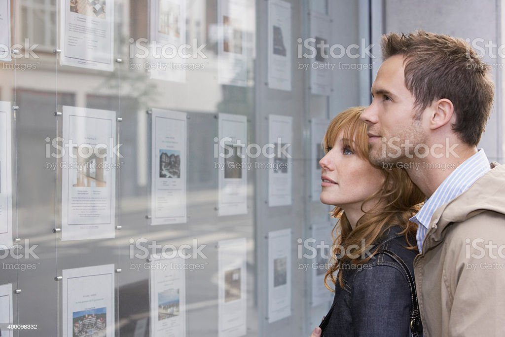 Couple Looking At Real Estate Office Display stock photo