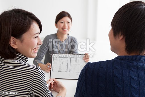 istock Couple looking at the blueprint in the office 516645468